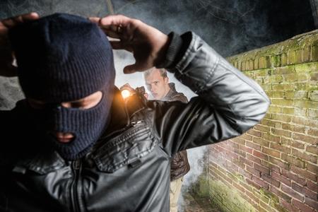 Police Officer Pointing Gun Towards Busted Masked Burglar photo