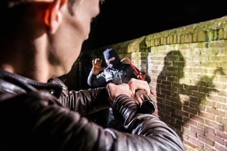 Police Officer Aiming Gun Towards Scared Burglar At Night photo