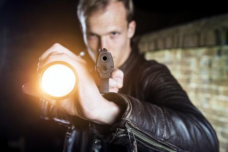 Plain Kleidung Strafverfolgungsbeamte halten ein Blitzlicht, und zeigte seine Waffe in die Kamera während einer Verhaftung in der Nacht