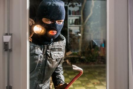 Einbrecher mit Taschenlampe und Crowbar Blick in Glasfenster