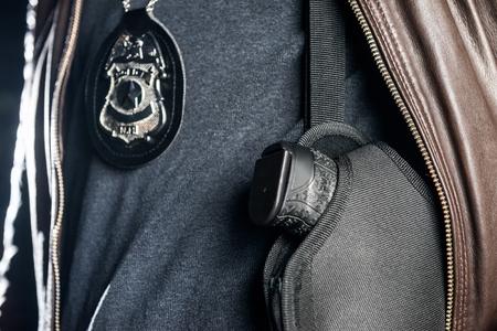 Nahaufnahme des Polizisten mit Abzeichen und Pistole Standard-Bild