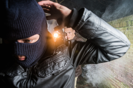 Policeman Aiming Pistol Towards Busted Gangster photo