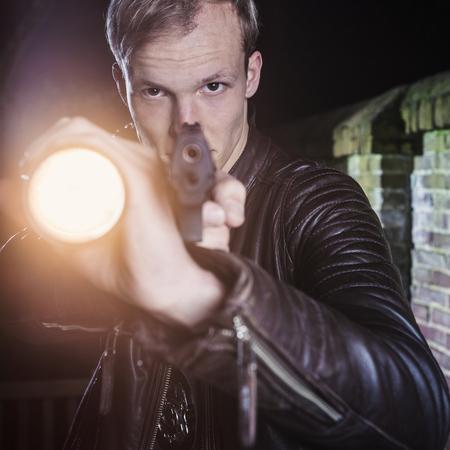 Special Agent in der Dämmerung, zeigt die Dämmerung seine Waffe und Taschenlampe auf Verdächtiger in einer Gasse