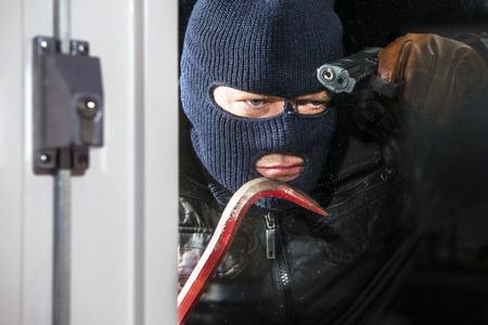 Bedrohlich suchen Eindringling, einen Kopfschutz trägt und einen Kuhfuß und Hand Pistole, durch das Fenster eines Hauses suchen, bereit zu brechen