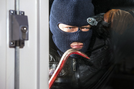 Menacing looking intruder, wearing a balaclava and holding a crow bar and hand gun, looking through the window of a house, ready to break in photo