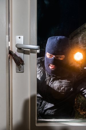 Intruder Holding Torch While Trying To Open Window With Crowbar photo
