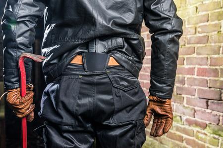 Gangster mit der Brechstange und Gewehr, die Wand nachts bereitstehen Standard-Bild