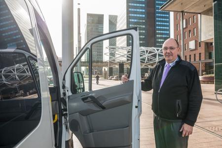 Porträt von zuversichtlich männlichen Taxifahrer stehend von van am Flughafen Standard-Bild
