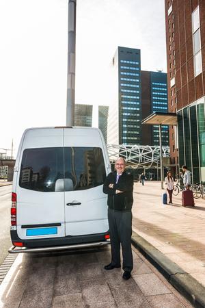 Porträt von stehenden Armen des Berufstaxifahrers kreuzte durch Packwagen am Flughafen