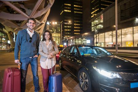 Porträt von lächelnden Paar mit Gepäck stehend mit dem Taxi auf Stadtstraße in der Nacht