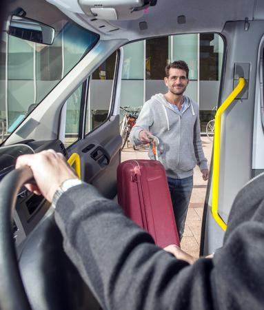 Lächelnder Mann, der einen Koffer trug, einen Minivan betrat, auf dem Weg zum Flughafen, seine Augen treffen und den Busfahrer grüßen. Standard-Bild
