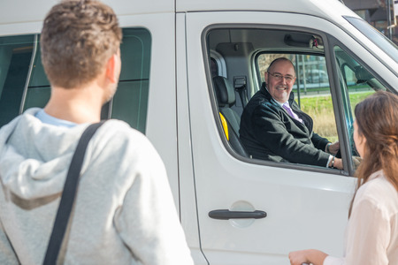 Smiling professional driver in van looking at passengers at airport Stockfoto