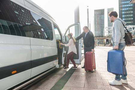 Taxifahrer mit Gepäck Unterstützung weiblichen Passagier an Bord van am Flughafen
