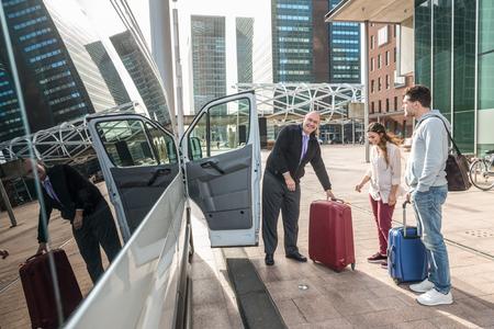 공항에서 밴으로 수하물을 탑승하는 전문 택시 운전사 및 승객