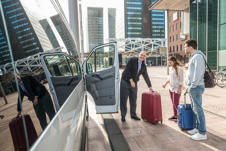 Professional cab driver and passengers with luggage by van at airport