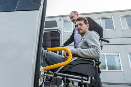 Untersicht der Profi-Taxifahrer Unterstützung behinderter Mann an Bord van außerhalb Gebäude Standard-Bild