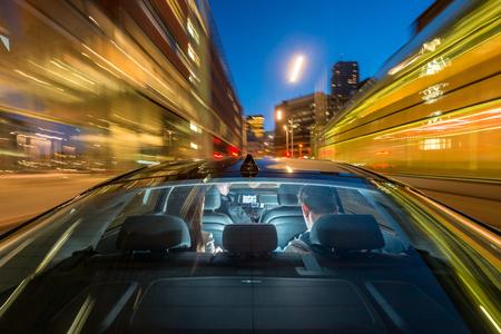 Verschwommene Bewegung der professionellen männlichen Taxifahrer reiten Paar auf Stadt Straße in der Nacht