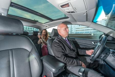 Professionelle Fahrer Taxi fahren während weiblichen Passagier Anwendung Lippenstift