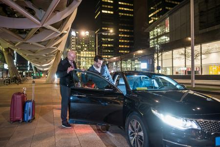 Männliche professionelle Fahrer helfen Passagier in das Auto auf Stadtstraße in der Nacht
