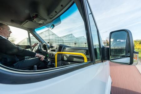 Seitenansicht der professionellen Taxifahrer fahren von Gewächshaus an sonnigen Tag