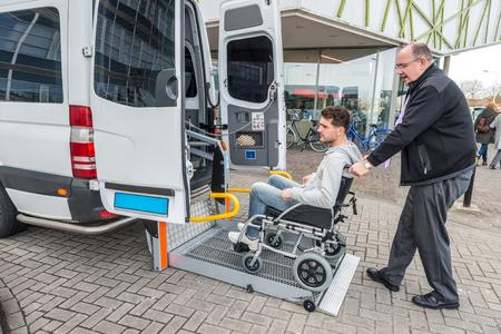 Zijaanzicht van taxichauffeur die een man op rolstoel helpt bij het bouwen van buitenbouwen Stockfoto