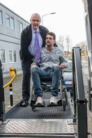 Taxifahrer, der den Mann auf dem Rollstuhl unterstützt, um den hydraulischen Hubwagen zu betätigen Standard-Bild