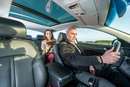 Professionelle Taxifahrer fahren Taxi während weiblichen Passagier mit digitalen Tablette