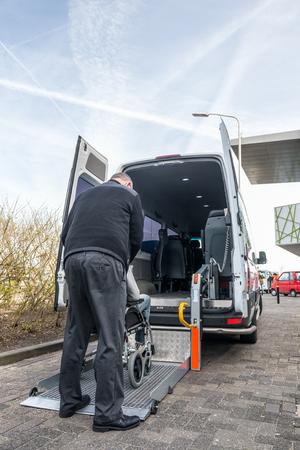 Achteraanzicht van taxichauffeur die een man op rolstoel helpt om aan te trekken hydraulische lift