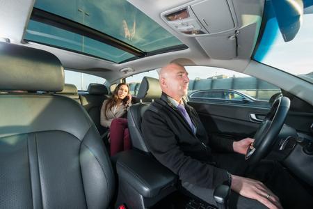 Professionele chauffeur rijden taxi terwijl vrouwelijke passagier praten op de mobiele telefoon Stockfoto