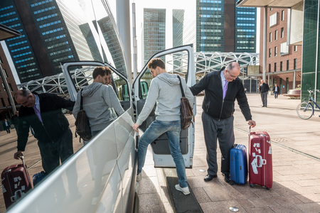 Taxi driver with luggage picking up male passenger at airport in city
