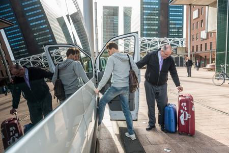 Taxifahrer mit Gepäck Abholung männlichen Passagier am Flughafen in der Stadt Standard-Bild