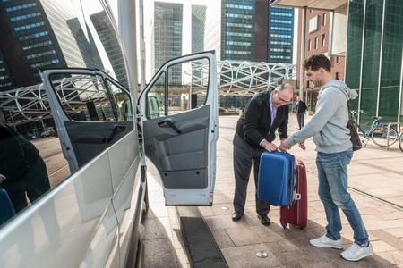 Taxifahrer unterstützt männlichen Passagier mit Gepäck von van am Flughafen Standard-Bild