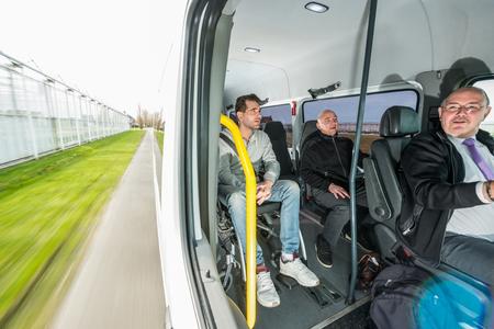 Professioneller Taxifahrer fährt männliche Passagiere zu ihrem Ziel