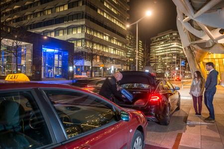 Taxifahrer lädt Passagiergepäck im Kofferraum auf Stadtstraße bei Nacht