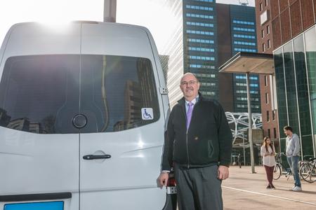 Porträt von zuversichtlich professionellen Taxifahrer stehend von van am Flughafen