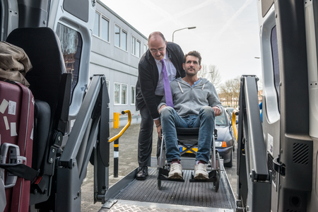 Professional cab driver assisting man on wheelchair to board hydraulic lift van
