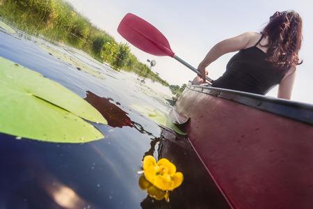 Frau sitzt in einem Kajak hausieren auf einem ruhigen Fluss mit grünen Ufern und gelbe Lilie