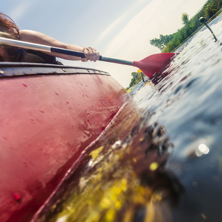 Frau Kanu auf einem Sommertag auf einem flachen Fluss