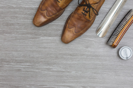 attributes to polisch your shoes, on a wooden floor, top view, copy space
