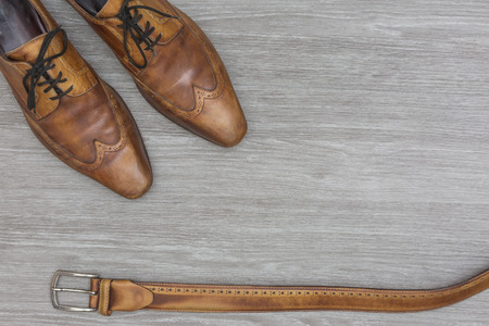 top view from matching men shoes and belt, on a wooden floor, top view
