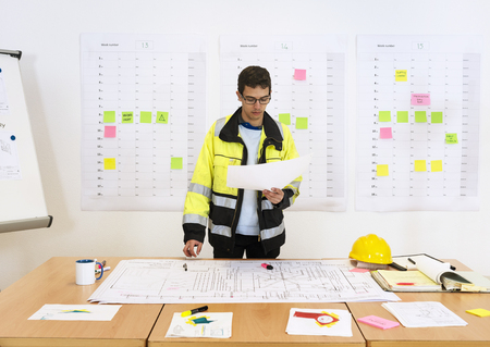 Worker checking techinical drawings at the office with a planboard with sticky notes and a flipover in the background