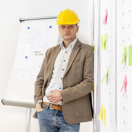 A senior engineer, wearing a hard hat leaning against a wall with several planning boards and sticky notes attached to it. Stockfoto