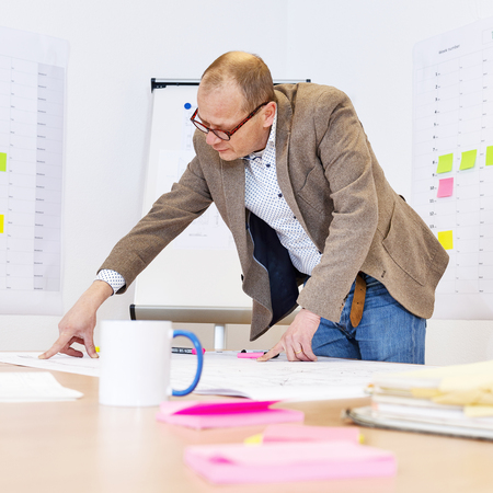 A Technical Manager is checking technical drawings,  with a planboard  with sticky notes and a whiteboard in the background.