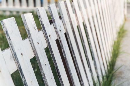 white fence made from wood on the grass photo