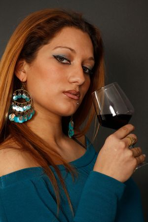 Spanish girl drinking wine from a glass in her right hand wearing big earrings