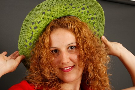 red head girl: Red head girl trying a green hat