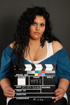 A black hair girl holding a movie clapper, take 1997 photo