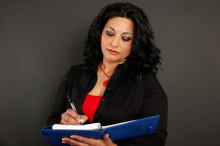 A brunette woman with a red and black shirt writing on a blue binder photo