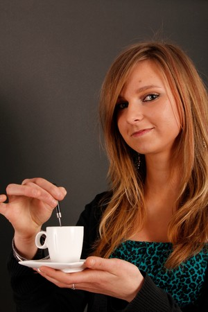 stiring: Studio shot of a beautiful young blond young girl enjoying a cup of coffee  Stock Photo