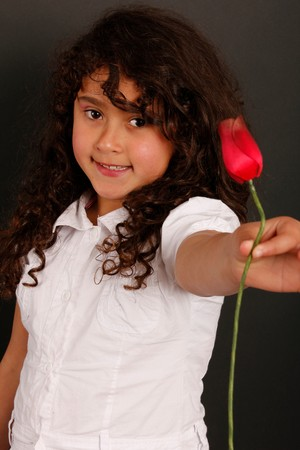 A cute little spanish girl offering a red tulip photo